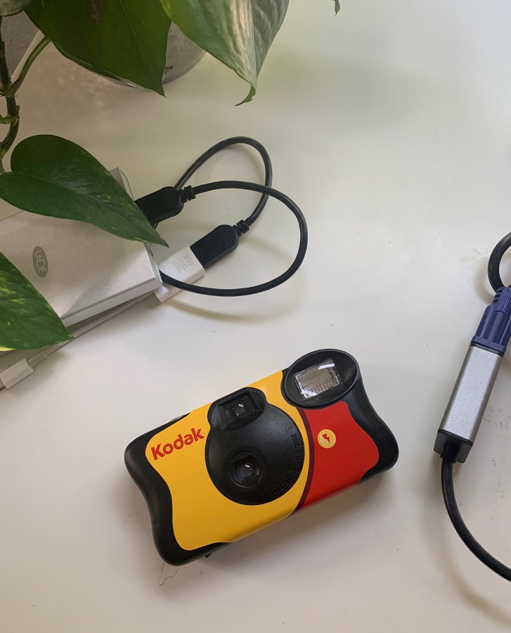 a red, yellow, and black classic kodak disposable camera on a white background with a plant, a hard drive, and a dongle visible in the top and right-hand margins of the image.
