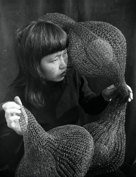 Ruth Asawa holding one of her early looped-wire sculptures, 1951