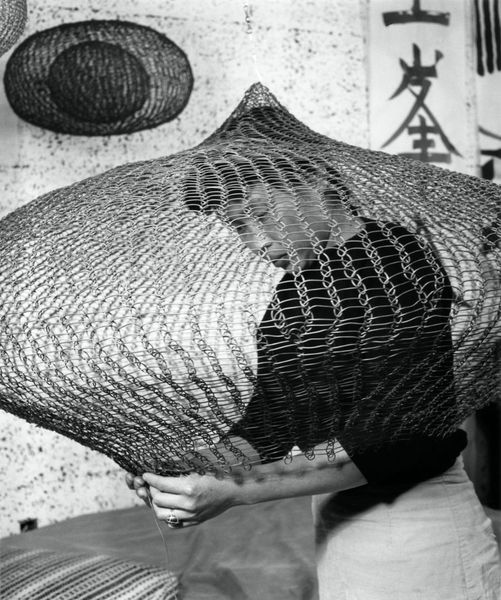 Portrait of Ruth Asawa working inside the lobe of a looped-wire sculpture, 1957