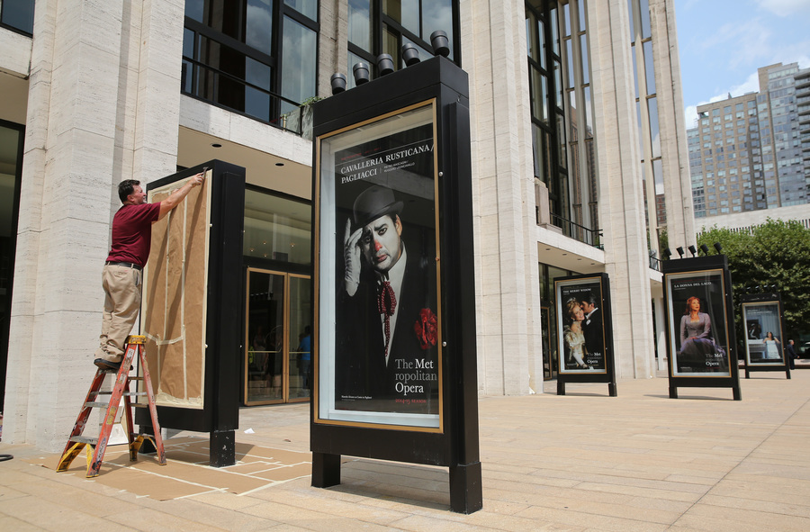 a-worker-unveils-advertisement-for-future-productions-at-the-metropolitan-opera-on-july-29-2014-at-lincoln-center-in-new-york-city-the-metropolitan-operas-general-manager-peter-gelb-has-threatened-a-lockout-at-the-end-of-july-if-there-is-no-an-agreem.jpg