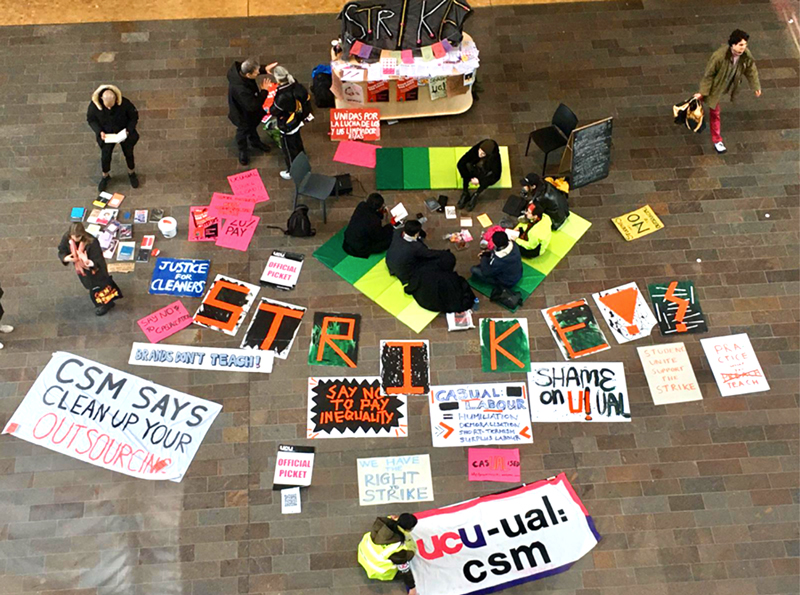 A photo of the CSM picket line, taken from above. There are people sitting on the ground for a teach-out, and colourful signs laid out on the ground.