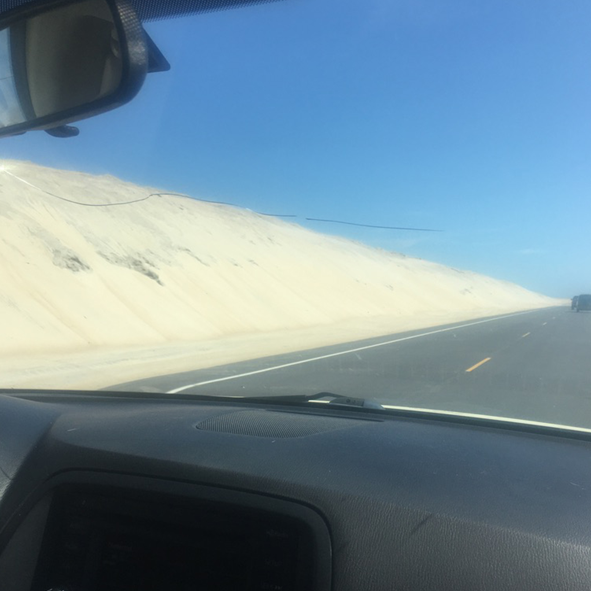 a road with a mountain of sand to the side, taken inside a car
